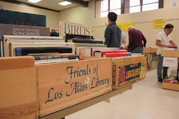 Boxes of books for sale, people in the background, label reads Friends of Los Altos Library