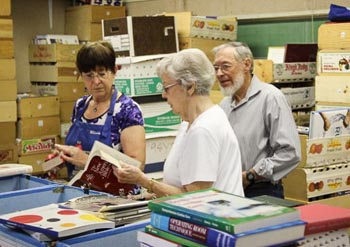 Three volunteers sorting books