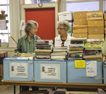 Two women in a room full of books